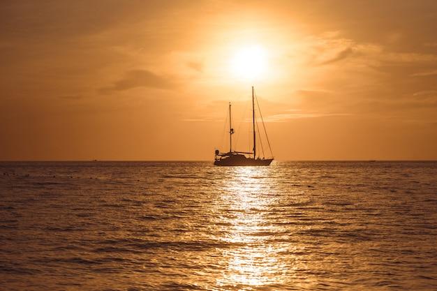 Yacht dans la mer tropicale au coucher du soleil