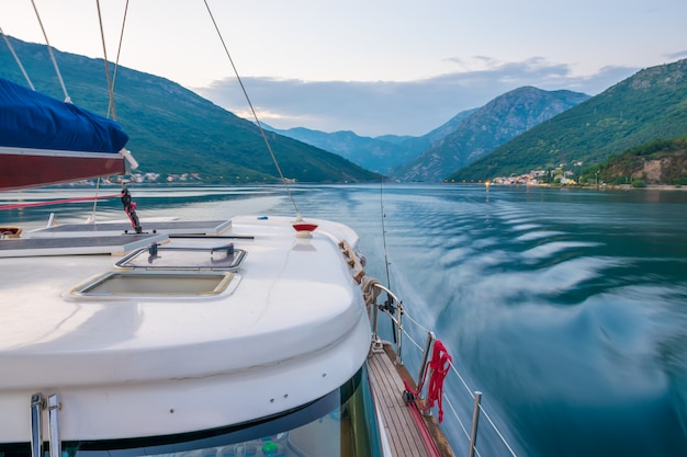 Un yacht de luxe navigue dans la baie le soir.