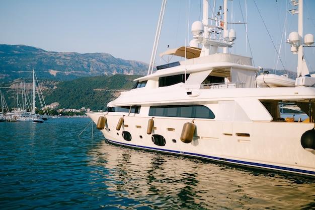 Yacht à moteur blanc de luxe navigue devant le quai du bateau de budva monténégro