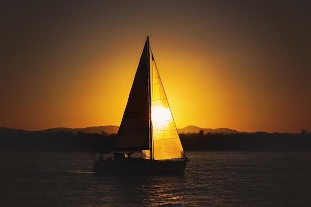 Yacht à voile contre le coucher du soleil