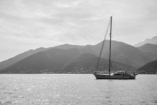 Yacht à voile avec grand mât dans la mer au large du rivage. paysage marin, photographie noir et blanc