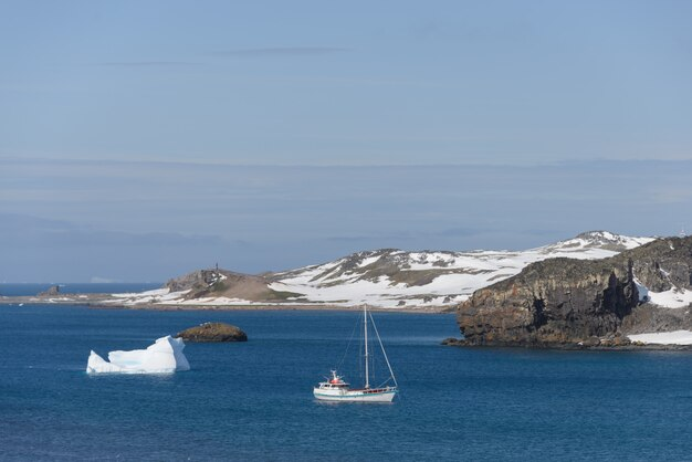 Yacht à voile et iceberg en mer antarctique