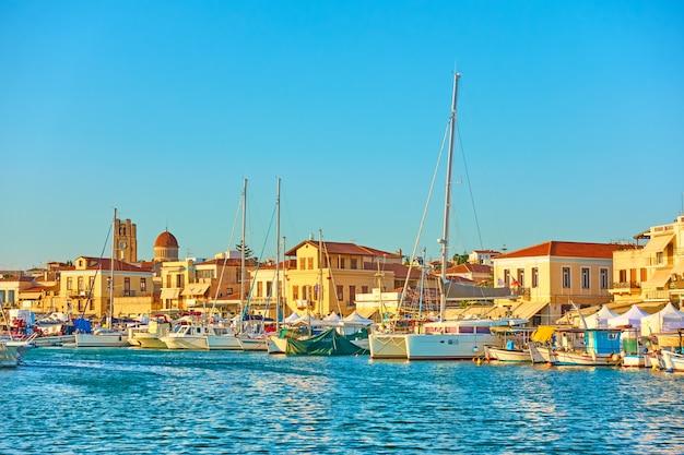 Yachts et bateaux dans le port et le front de mer de la ville d'égine au coucher du soleil, l'île d'égine, grèce