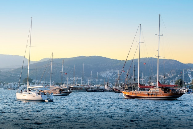 Yachts de luxe amarrés dans la marina au coucher du soleil.
