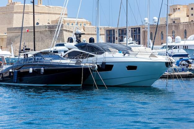 Des yachts à moteur modernes blancs et noirs sont amarrés au port sur fond de paysage urbain.