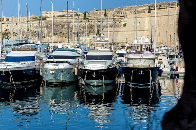 Des yachts à moteur modernes blancs et noirs sont amarrés au port sur le paysage urbain