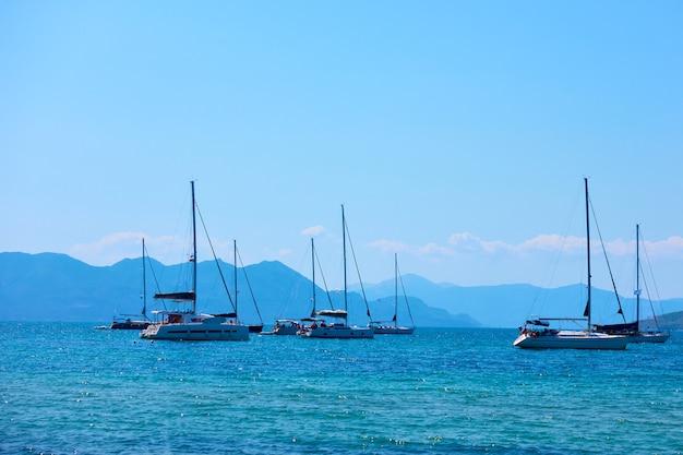 Yachts à voile dans la mer près de l'île d'égine à midi d'été, îles saroniques, grèce