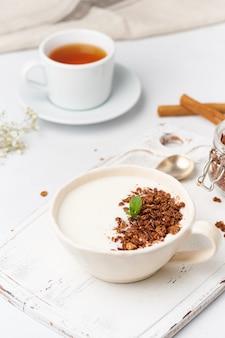 Yaourt au chocolat granola en coupe, petit déjeuner avec du thé sur un fond en bois blanc, vertical.