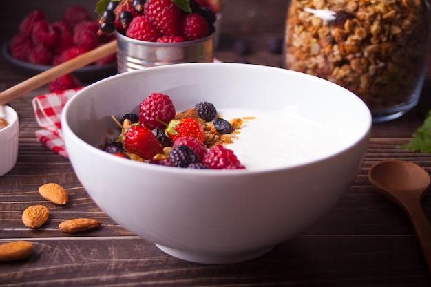 Yaourt aux baies fraîches, granola d'avoine muesli sur la table en bois. concept de petit-déjeuner sain.