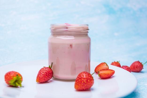Yaourt aux fraises sur plaque blanche avec des fraises