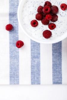Yaourt aux graines de chia et framboises fraîches. petit-déjeuner estival