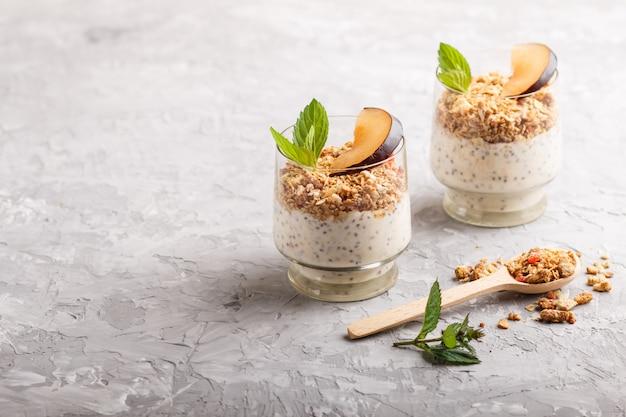 Yaourt aux prunes, graines de chia et granola dans un verre et une cuillère en bois. vue de côté