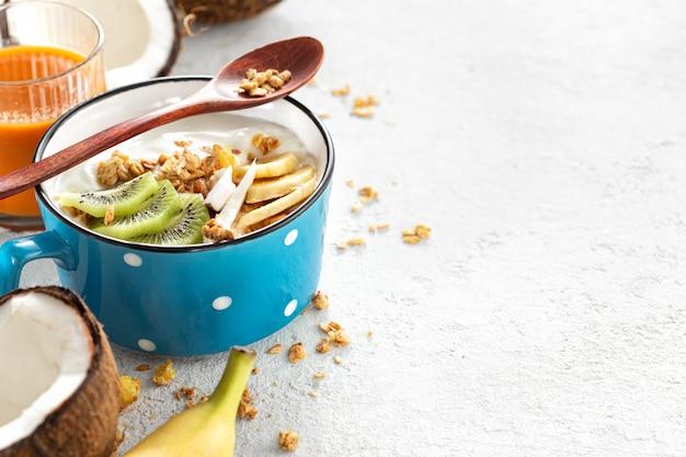 Yaourt bio à la noix de coco avec granola et kiwi de fruits et bananes en tasse avec copie espace