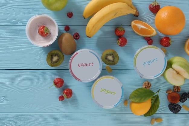 Yaourt dans un récipient avec des fruits tropicaux sur un fond en bois, vue de dessus. concept d'alimentation saine