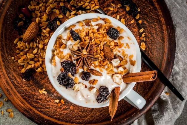 Yaourt épicé avec granola, baies séchées, noix, amandes, épices