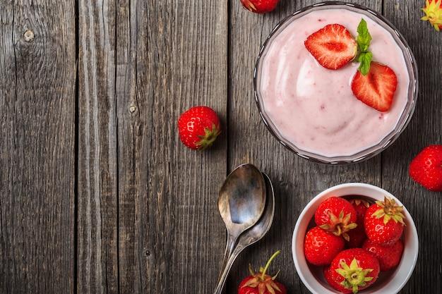 Yaourt fait maison avec des fraises fraîches sur un bois
