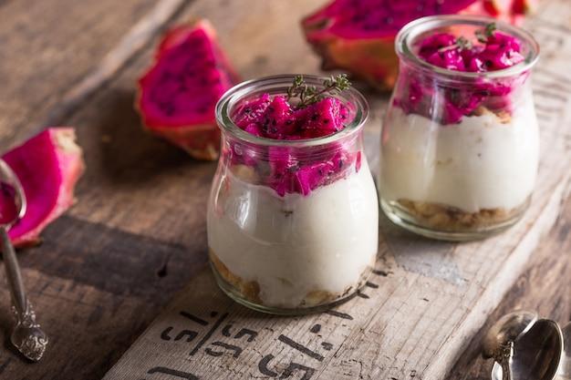 Yaourt fait maison avec des fruits du dragon mûr, pitaya ou pitahaya sur fond de bois, concept sain de fruits