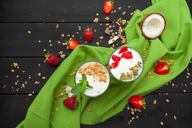 Yaourt fait maison avec granola, fruits et noix de coco vue de dessus sur bois