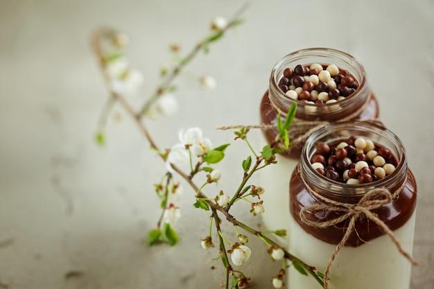 Yaourt fait maison avec mousse au chocolat et gouttes de bonbons au chocolat avec branche de printemps.