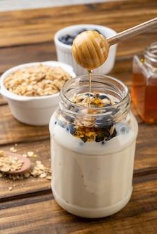 Yaourt, granola, myrtille et miel sur table en bois. ustensile en bois versant du miel.