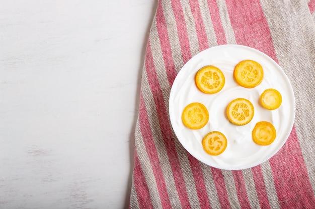 Yaourt grec avec des morceaux de kumquat dans une assiette blanche