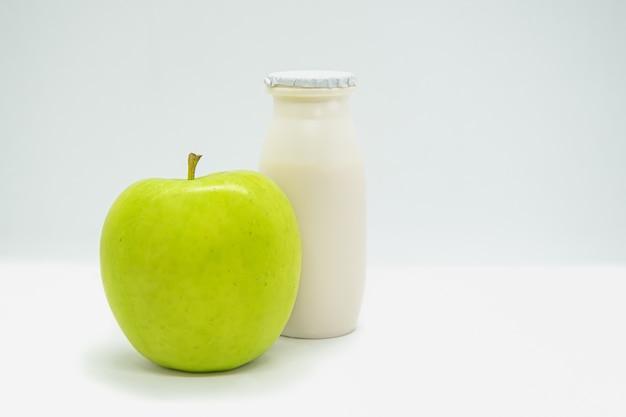 Yaourt liquide naturel avec des probiotiques dans une petite bouteille en plastique et pomme verte sur blanc