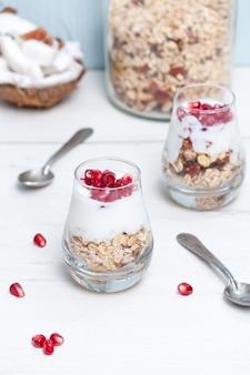Yaourt maison avec du granola et des fruits de grenade dans des verres sur une table en bois blanc