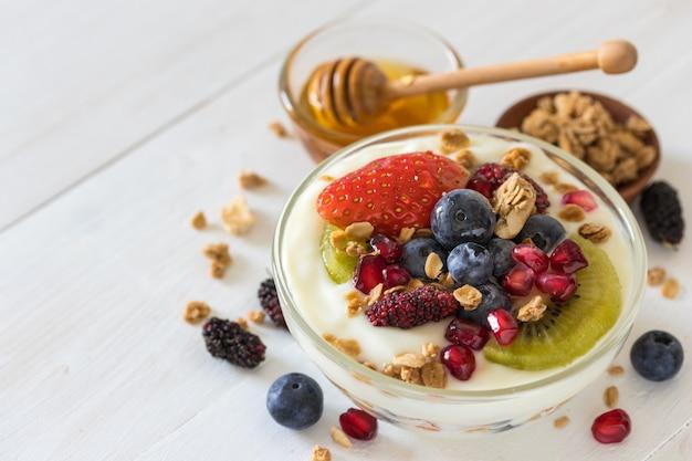 Yaourt nature avec fraises, myrtilles, kiwi, granola, grenade dans un bol en verre