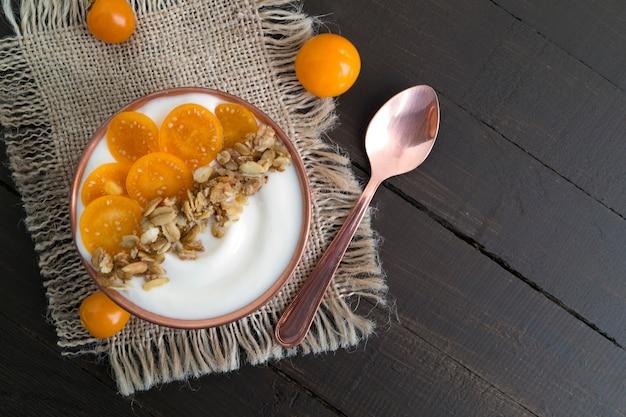 Yaourt naturel avec cerise de terre sur une table en bois.