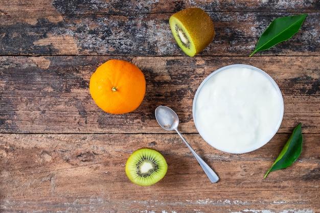 Yaourt naturel et fruits sur une table en bois
