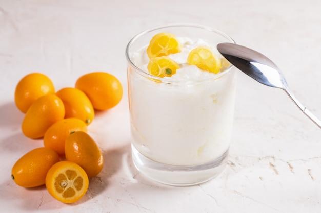Yaourt avec des tranches de kumquat en verre avec une cuillère en métal et des fruits entiers