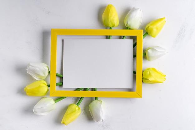 Yellowtulips avec cadre photo vierge sur fond de marbre blanc, espace copie