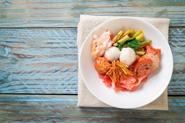 (yen-ta-four) - nouilles sèches de style thaïlandais avec un assortiment de tofu et une boule de poisson dans une soupe rouge