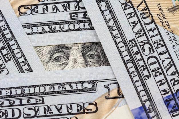 Les yeux de benjamin franklin entre des billets de cent dollars