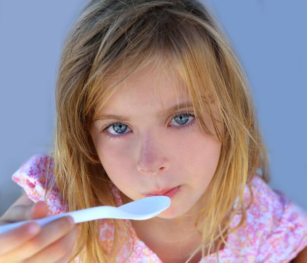 Yeux bleus kid fille avoir déjeuné avec cuillère