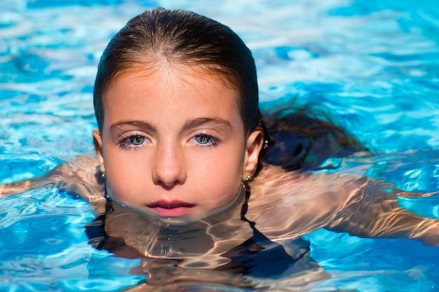 Yeux bleus kid fille à la piscine face à la surface de l'eau