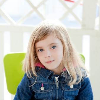 Yeux bleus kid fille portrait en plein air s'asseoir sur une chaise