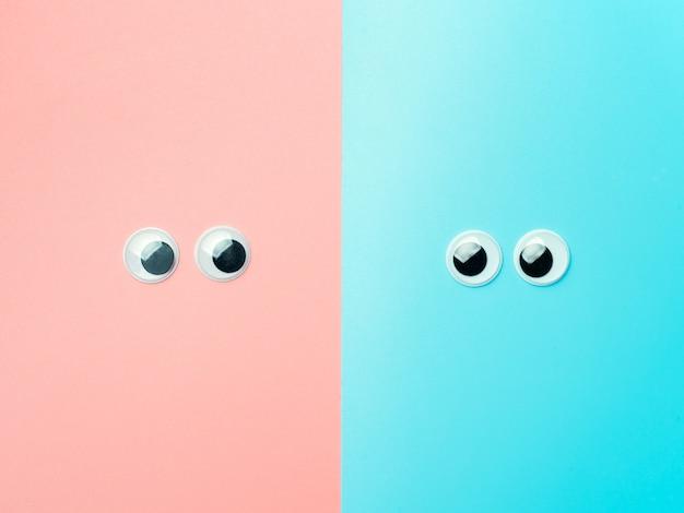 Yeux écarquillés sur fond bleu et rose. vue de dessus ou pose à plat. yeux de jouet en plastique sur fond turquoise