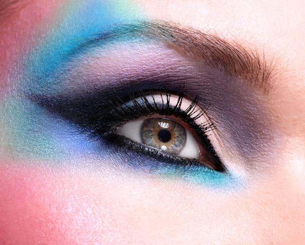 Yeux de femme gros plan avec beau maquillage bleu vif de mode