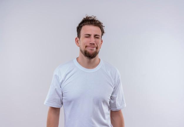 Avec les yeux fermés désolé jeune homme vêtu d'un t-shirt blanc sur un mur blanc isolé