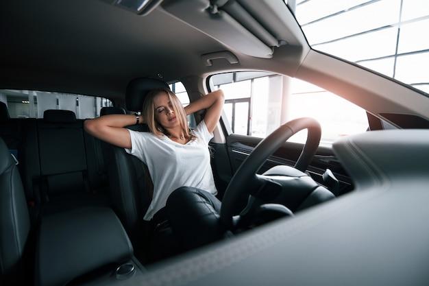 Les yeux fermés. fille en voiture moderne dans le salon. le jour à l'intérieur. acheter un véhicule neuf