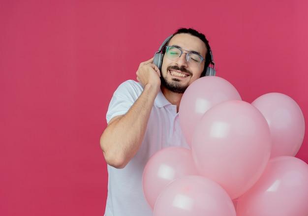 Avec les yeux fermés heureux bel homme portant des lunettes tenant des ballons et écouter de la musique sur un casque isolé sur rose