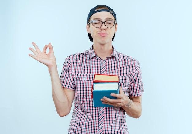 Avec les yeux fermés heureux jeune étudiant garçon portant un sac à dos et des lunettes et une casquette tenant des livres et montrant le geste okey sur blanc