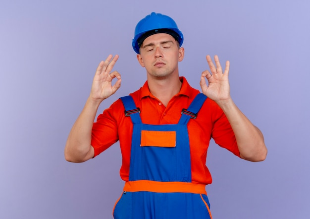 Avec les yeux fermés jeune constructeur de sexe masculin portant l'uniforme et un casque de sécurité montrant le geste okey sur violet