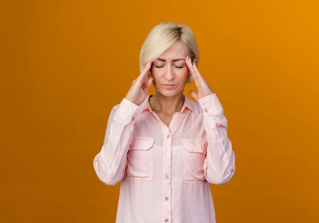 Avec les yeux fermés jeune femme slave blonde mettant les mains sur le temple isolé sur mur orange