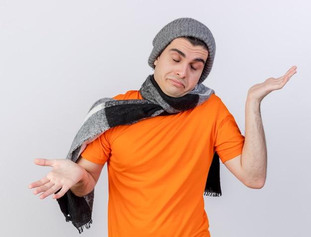 Avec les yeux fermés jeune homme malade portant un chapeau d'hiver avec écharpe répandre les mains isolé sur fond blanc