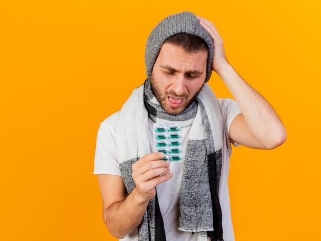 Avec les yeux fermés jeune homme malade portant un chapeau d'hiver et une écharpe tenant des pilules et montrant la langue mettant la main sur la tête isolé sur fond jaune