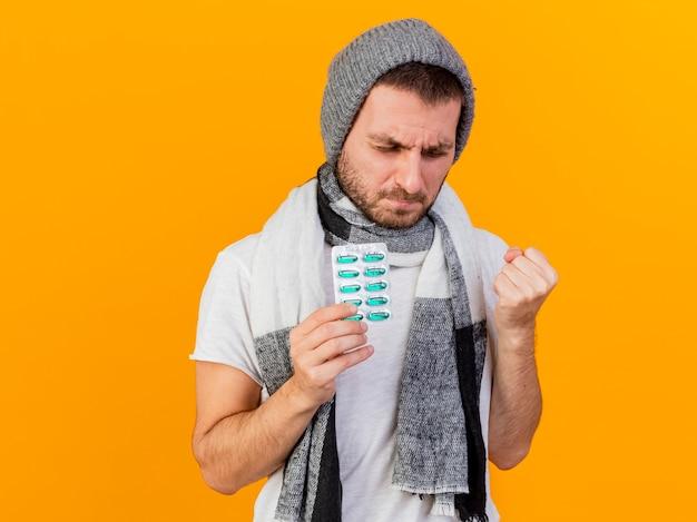 Avec les yeux fermés jeune homme malade portant un chapeau d'hiver et une écharpe tenant des pilules et montrant oui geste isolé sur fond jaune