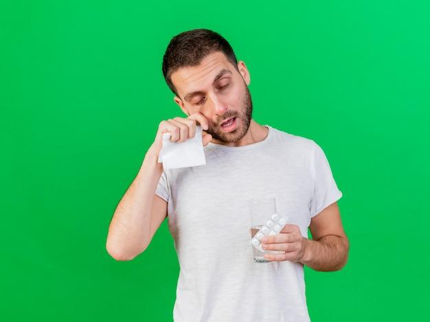 Avec les yeux fermés jeune homme malade tenant un verre d'eau avec des pilules et essuyant les yeux avec la main isolé sur fond vert