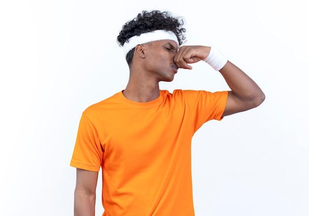 Avec les yeux fermés jeune homme sportif afro-américain dégoûté portant un bandeau et un bracelet nez fermé